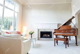 helles tageslicht das in wohnzimmer mit brennendem kamin flügel und weißem ledernem sofa kommt