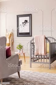 poster an der wand mit formteil und sessel im kinderzimmer schlafzimmer innenraum mit grauen wiege echtes foto stockfoto und mehr bilder babybett