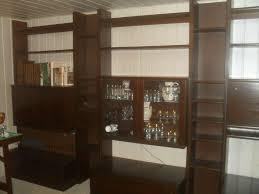 wohnzimmer dunkles holz komplett mit regalen tischen