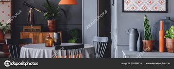 Close Up Photo Of Dining Table With Vases And Fresh Plants Vessels Standing On Cupboard In Dark Room Interior By Photographeeeu