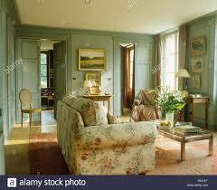 geblümten sofa und couchtisch aus glas in blau grün