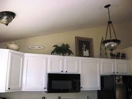 How To Decorate Above Kitchen Cabinets Dark Table Sets Black Iron Stove Brown Color Granite Countertop