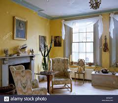 country style gelb wohnzimmer kamin und sesseln fenster mit