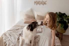 lächelndes kleines mädchen streichelt ihren hund im