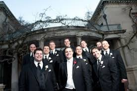 Groom In Black Tuxedo White Vest Red Rose Boutonniere With Groomsmen Tuxedos