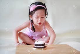 nettes kleines mädchen das kleine geburtstagskerzen auf kuchen 2 jahre alte feiernde kinder durchbrennt