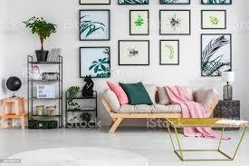 gold metalltisch stehend in weiß wohnzimmer interieur mit dekor auf schwarzem metall gestellen frischen grünpflanzen leicht graue sofa mit kissen und