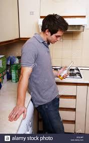 junger mann in der küche die flasche bier trinken