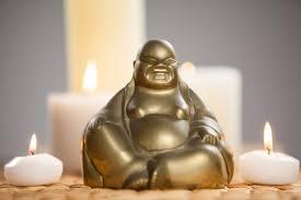 rire figurine buddha et des bougies allumées sur le tapis