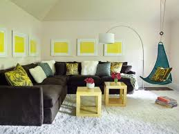 Yellow And Brown Family Room In Attic Features Cream Walls Lined With A Series Of Framed Art Over Dark Velvet Sectional Adorned