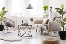schwarzer tisch auf weißem runden teppich im hellen wohnzimmer mit stuhl und sofa neben pflanze und puff