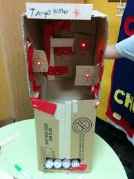 A Cardboard Arcade Game With An Automatic Ball Return And Light Up Targets