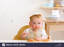 Messy Baby Boy In High Chair With Bowl Of Spaghetti On Head ...