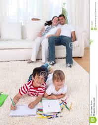 kinder die auf fußboden im wohnzimmer malen stockbild
