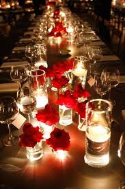 Multiple Single Red Roses And Candles Spread Down The Length Of Table