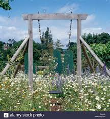Rustic Swing Set Among White Daisies In Wild Flower Garden