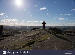 Single Person Standing On Cliff Edge Looking Out At The Scenery In Derbyshire England