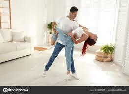 schönes junges paar tanzt im wohnzimmer stockfotografie
