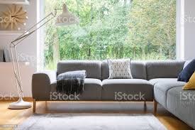große weiße metall le stand neben grauen ecke lounge mit decke und kissen im innern echtphoto helles wohnzimmer mit fenster stockfoto und mehr