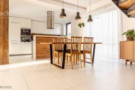 geräumige offene küche und esszimmer mit hölzernen tisch und stühle große fenster weiße schränke und fliesen auf dem fußboden echtes foto stockfoto