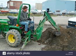 Adult Male Construction Worker Uses Back Hoe To Dig A Trench Lay Electrical Lines