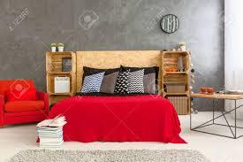 modern gestaltete schlafzimmer mit roten bett und sessel auf dem hintergrund graue wand holzböden aus holzkisten und kopfteil aus holz auf dem bett