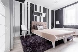 weißes und schwarzes schlafzimmer mit streifenwand und flauschigem teppichboden