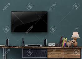 led tv auf dunkelgrüne wand mit medienmöbel im wohnzimmer