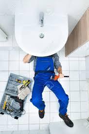 erhöhte ansicht der männlichen klempner reparatur einer spüle im badezimmer