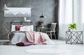 pflanze auf designer tisch im hellen schlafzimmer mit grauen und rosa bettwäsche auf bett im schlafzimmer mit arbeitsbereich und poster an der wand