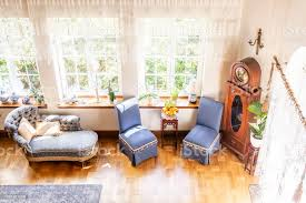 hohen winkel eine silberne lounge blaue stühle und hölzerne uhr stehen neben fenstern in luxuriösen englischen stil wohnzimmer eingerichtet echtes