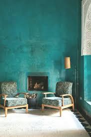 wandfarbe petrol wohnzimmer minimalistisch kamin sessel