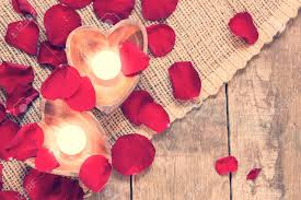 Enlightened Candles In Heart Shaped Candleholders With Red Roses Petals On Rustic Wooden Background