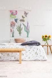 ferienhaus haus minimal schlafzimmer innenraum mit bunten blumen und vögel gemalt auf stoff über ein bett das in naturtextilien blätter gekleidet ist