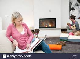 Woman Reading A Magazine With Her Family In A Living Room Stock