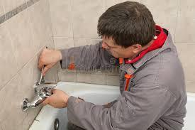 klempner arbeitet in einem badezimmer stockbild bild