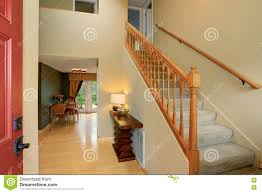 Entrance Hallway In Ivory Tones With View Of Staircase And Dining Table Set