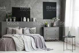 leinwand auf eine graue wand in einem interieur monochromatische gemütliches schlafzimmer mit einem bett mit kissen und bettwäsche mond eine decke