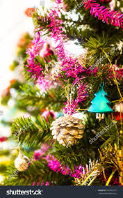 Beautiful Green Christmas Tree With Santa Cross Doll Colorful Balls Gift Of Pine Trees And Ribbons Set Aside To The Concrete Wall At Day Blur