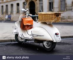 White Vespa Classic Scooter With Basket Parked Outside Of Buildings