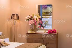 innere des weiblichen schlafzimmer beige wände eine hölzerne kommode blumen dekor gold stehleuchte ein luxusspiegel stockfoto und mehr bilder