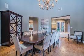 The Dining Room Looks Simple With Its Hardwood Flooring And Set Chandelier Lights Up