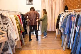 A Shopper And Salesperson Trying On Vintage Clothing In Store