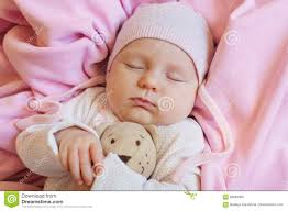 sweet little newborn baby sleeping on the blanket with his teddy