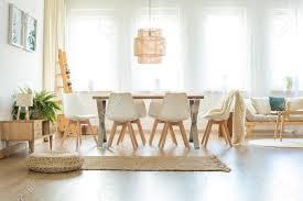 hocker und brauner teppich in geräumigen hellen esszimmer mit le über tisch und stühlen