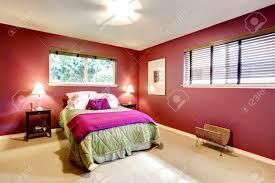 elegantes schlafzimmer mit beigen teppichboden und kontrastfarbe leuchtend roten wänden grün und lila bettwäsche harmonieren perfekt mit roten wand