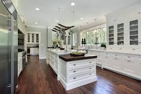 Luxury White Kitchen With Marble Island Hanging Pots And Pans Hardwood Flooring