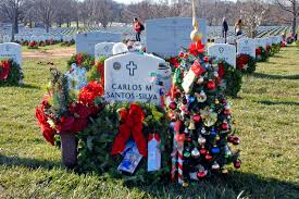 A Wreath Flowers And Small Christmas Tree Are Placed At The Grave Marker Of
