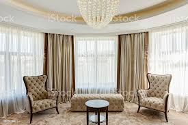 wohnzimmer mit großen fenstern in den farben beige und braun klassisches interieur der zimmer mit beige sofa zwei sesseln und runden holztisch und