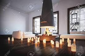 romantisches wohnzimmer mit brennenden kerzen auf einem dunklen holzfußboden der einen zentralen herd mit loderndem feuer und zwei bequemen sofas